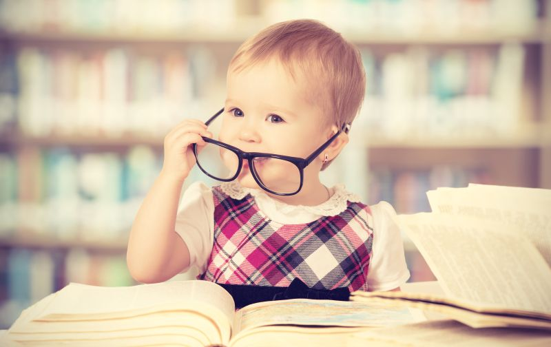 Baby with glasses and a book